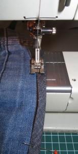 Naai het band aan de buitenkant van de broekspijp vast. Zo dicht mogelijk tegen de rand van het band.